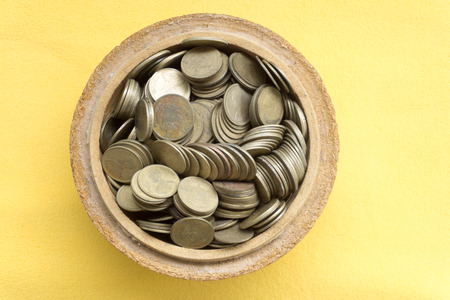 filled: Old bowl filled with Thai baht coin