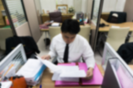 experiencing: Blur business man working at office with documents on his desk.