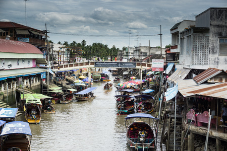 SAMUT SONGKHRAM, THAILAND - JULY 22, 2017 : AMPHAWA FLOATING MARKET, on weekends, the Amphawa Canal brims with boats loaded with drinks like O-Liang (Thai iced black coffee) and food such as fried sea mussels, noodles, and sweets. Bank-side wheelbarrows a