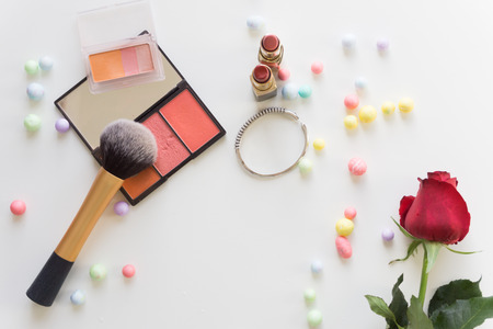 Top view make up with colorful balls and red rose on white background.