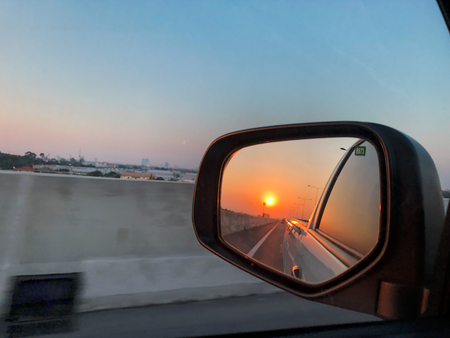 Beautiful sunset reflect in mirror of car.