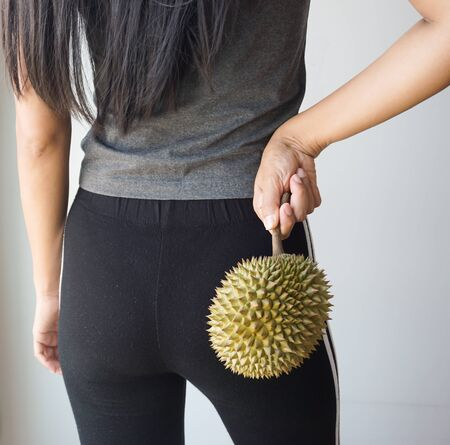 Asian woman holding durian on the back, Health concept. Stock Photo