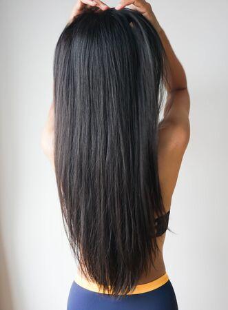 Mujer joven asiática con hermoso cabello largo y liso negro. Foto de archivo
