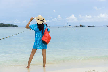 Woman in a blue dress Carrying red bag and one hand on the hat, Stand on the white beaches of Phi Phi Island Krabi Province, Thailand.
