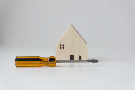 Orange-black screwdriver and small white wooden house. White background. Home improvement ideas.