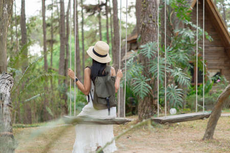 A female Asian tourist in white dress sits on a swing, and enjoys a vacation in pine forest at Doi Bo Luang, Chiang Mai, Thailand.