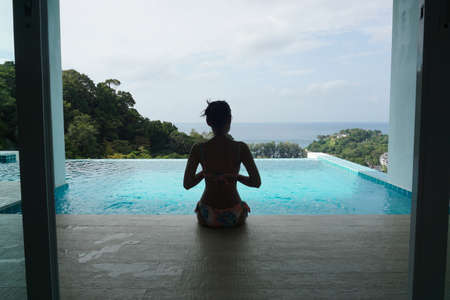 Slim young woman in bikini sitting on the edge of the swimming pool and looking at sea view.
