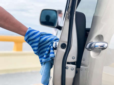 A Man cleaning car with microfiber cloth.