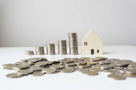 White wooden houses with silver coins stacked in order of height, scattered coins on the front, white background, business concepts, business growth.