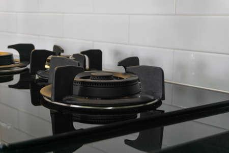 Burner black gas hob of a white modern kitchen.