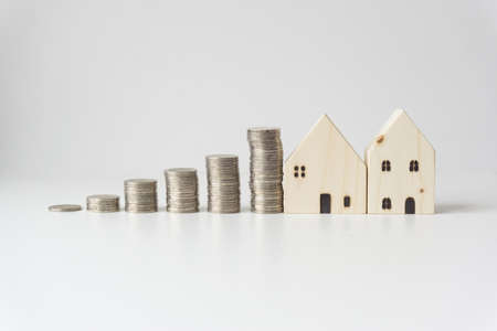 Silver coins stacked with 2 white wooden houses, business ideas. 版權商用圖片