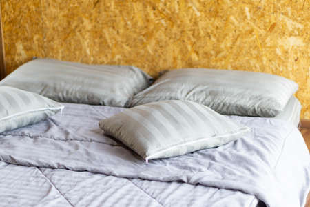 Comfortable soft pillows and blanket on empty bed.