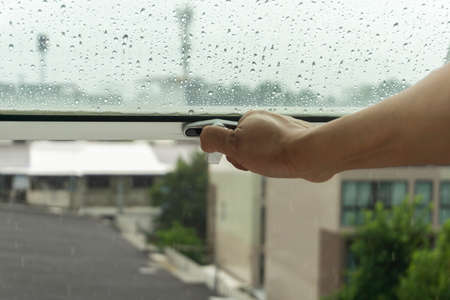 The woman's hand was closing the window because of the rain.