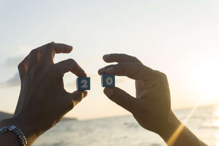 Man and women holds a Number two and zero in hands, sunset, sea background. 版權商用圖片