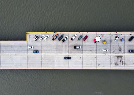 Top view of Many cars park on the bridge, and people take vacations such as taking pictures and sitting there.