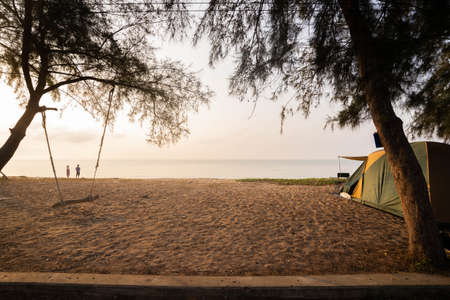 In the morning tents and swings under the pine trees at the beach, couples stand happily at the beach on vacation.