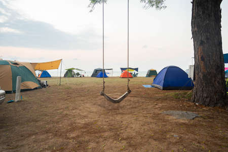 Asian tourists pitch a tent on the seashore on vacation, swings tied to a large pine tree.