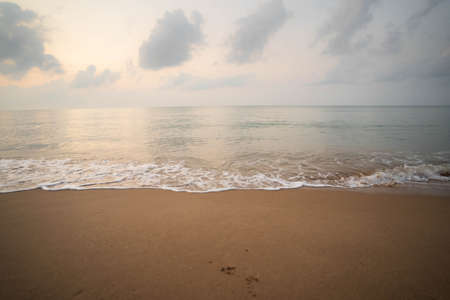 Sky and sea waves on brown sand in the morning. 版權商用圖片