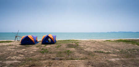 Beautiful sky and blue sea and 2 yellow-blue tents at the beaches in the morning. 版權商用圖片