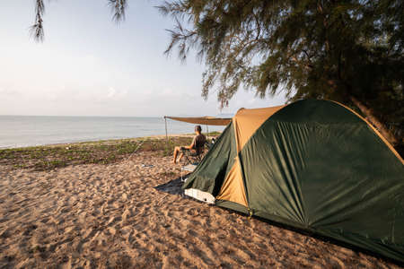 A tourist Asian man sits on a camping chair in front of a tent, looking at the beauty of the sea in the morning, happy holidays.