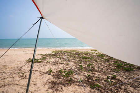 Tent poles and sunshades during the day at the seashore, pitch a tent on vacation.