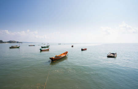 Beautiful blue sky and fishing boat anchored on the shore of the sea in Thailand.