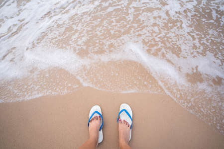 A woman wearing white sandals Stand on the beach with white waves.