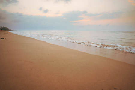 Yellow light sky and white waves on the beach in the morning, Thailand. 版權商用圖片