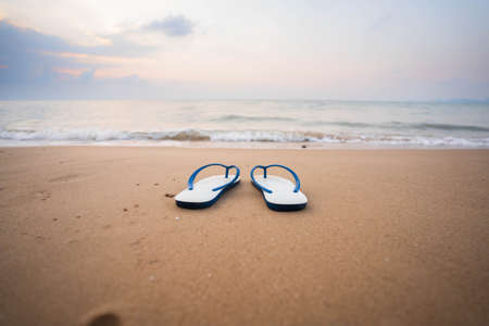 White sandals on the beach, white waves in the morning, conceptTourism.