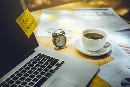 computer notebook, clock, cup of coffee and graphs papers put on wooden table. there is post it paper and wording Good Morning on laptop screen.