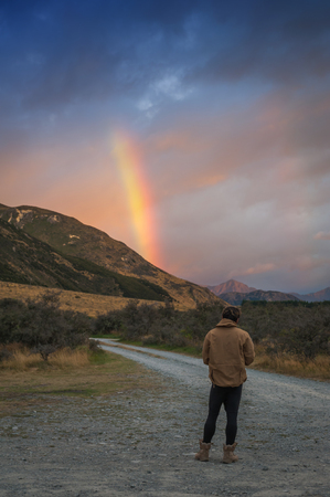 valley view: Man looking at rainbow over mountain near Lake Pearson  Moana Rua Wildlife Refuge located in Craigieburn Forest Park in Canterbury region, South Island of New Zealand Stock Photo