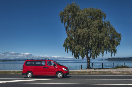 Taupo, New Zealand - March 2 2015: Lake Taupo in North Island of New Zealand with a red van driving pass Editorial