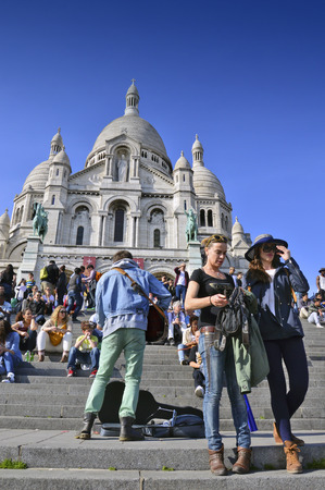 PARIS, FRANCE - 20 APRIL 2015: Tourists visiting the Basilica of the Sacred Heart of Paris, a Roman Catholic church and minor basilica, located at the summit of the butte Montmartre, the highest point of Paris