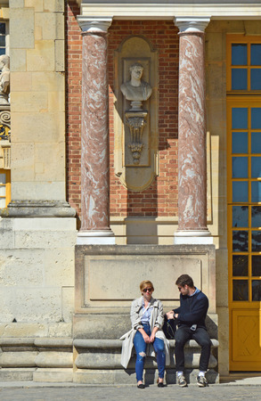 louis the rich heritage: VERSAILLES, FRANCE - April 19, 2015: A couple of tourists sitting outside the Palace of Versailles, UNESCO list of World Heritage Sites, in the city of Versailles, France.