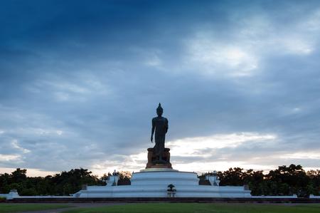 Walking Buddha statue at Buddhamonthon (Phutthamonthon), Buddhist Park in Nakhon Pathom, Thailand, in twilight moment