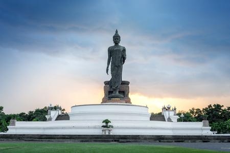 Buddha image in walking posture at Buddhamonthon (Phutthamonthon), Buddhist Park in Nakhon Pathom, Thailand, in twilight moment