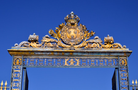 louis the rich heritage: VERSAILLES, FRANCE - April 19, 2015: Golden Main Gates of the Versailles Palace. The Palace Versailles was a royal chateau. It was added to the UNESCO list of World Heritage Sites. Paris, France.