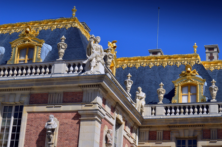 VERSAILLES, FRANCE - April 19, 2015: Beautiful roof details with golden ornaments and statues of Palace of Versailles
