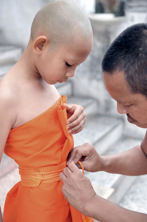 ordinate: Samut Songkhram, THAILAND - December 2011: Old Buddhist monk helps young novice monk wearing yellow robe during the ordinate ceremony