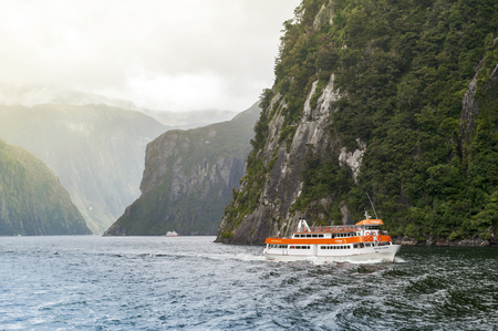 milford: Milford Sound, New Zealand - February 2016: Tourist boat cruises in the fjord of Milford Sound, South island of New Zealand