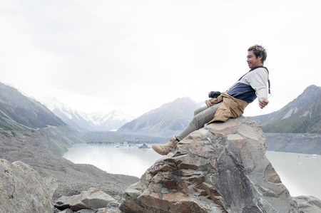 A man at Tasman Glacier viewpoint where New Zealand�??s longest glacier begins and the lower reaches where the ice meets the terminal lake, Aoraki  Mount Cook National Park