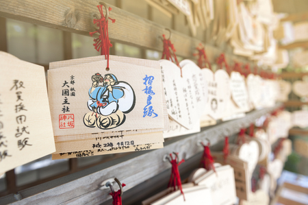 Kyoto, Japan - March 2016: Japanese Ema or small wooden votive plaques on which Shinto worshippers write their prayers or wishes then left hanging up at a shrine