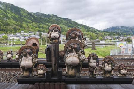 Kameoka, Japan - March 2016: Statues of Japanese raccoon dog or tanuki at Torokko Kameoka Station, terminal station for Sagano Scenic Railway or romantic train from Arashiyama