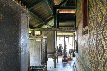Yasothon, Thailand - May 2017: Interior decoration with gilded black lacquer or Lai Rod Nam on walls and scripture cabinets inside Ho Trai or the Buddhist scriptures (Tripitaka or Pali Canon) library located at Wat Mahathat Temple Stock Photo - 79431539
