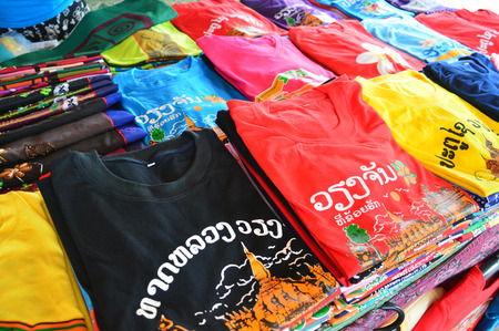 "Colorful t-shirts with Lao tourist attractions screen printing sold at souvenir shop in Vientiane, capital city of Lao PDR. Lao texts translated as ""That Luang Vientiane"", ""Vientiane"", and ""Patuxay"" Imagens"