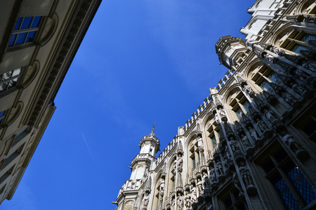 Low angle view of the Town Hall of the City of Brussels, a building of gothic architectural style from the middle ages located at the Grand Place in Brussels, Belgium