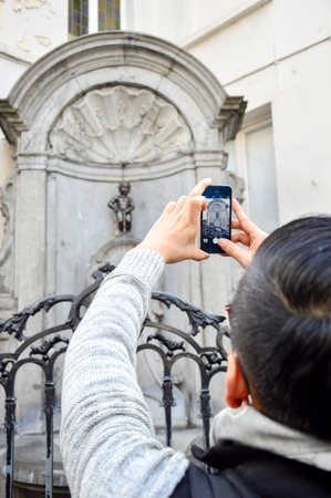Brussels, Belgium - April 2015: Tourist taking photo of Manneken Pis or Little Man Pee, a landmark small bronze sculpture designed by Hiëronymus Duquesnoy the Elder, located near Grand Place in the city of Brussels, Belgium