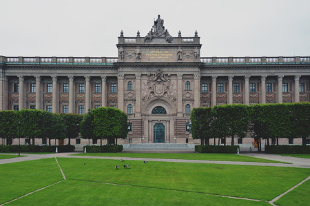 Building of The Parliament House of Sweden built in Neoclassical style, with a centered Baroque Revival style facade section, located on nearly half of Helgeandsholmen island, in the Gamla stan, old town district of central Stockholm
