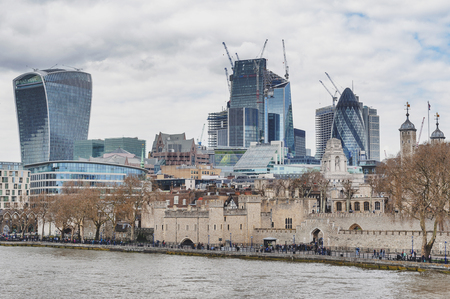 London, UK - April 2018: Tower of London located by the River Thames with skyscrapers and buildings constructed in modern architectural style rising up the behind skyline Editorial