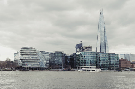London, UK - April 2018: The curved glass building in spherical shape of the City Hall of London and The Shard, the tallest building in the UK, iconic architectural landmarks of London located on the Southwark bank of the River Thames near Tower Bridge, E